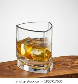glass of whisky with ice on a wooden table isolated on a white background