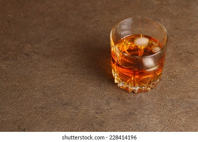 Glass of whisky with ice standing on a wooden tabletop