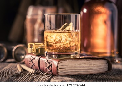 Glass of whisky with journal, compass and binocular