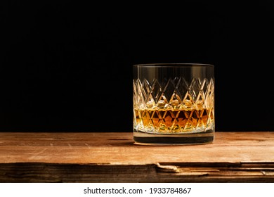 A glass of whisky on a wooden table on a dark background