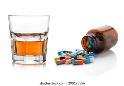 Glass of whisky and pills capsules on white background.