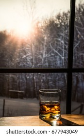 Glass of Whisky sitting on a wood table looking out on snow covered woods