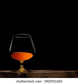 a glass of whisky with wooden box on black background
