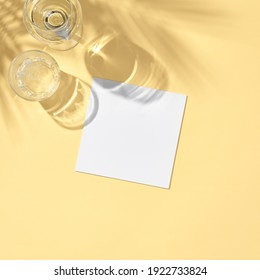 Glass with white paper card flat lay. Pastel yellow table in sunlight with palm leaf shadow. Wedding, birthday, tropical summer day concept.