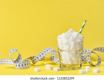 Glass with white sugar cubes and measuring tape. Weight control, diet and detox concept
