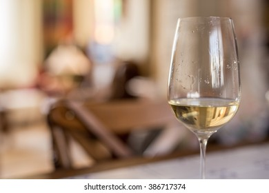 Glass of white wine against defocused background, closeup shot