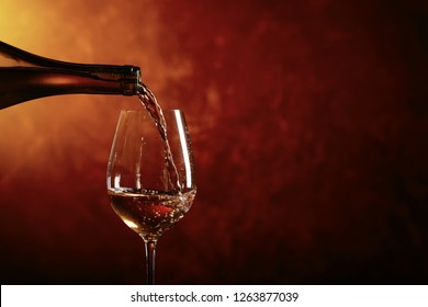 Glass of white wine being poured from a bottle . Copy space for your text .