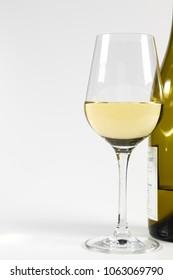 A glass of white wine beside a wine bottle