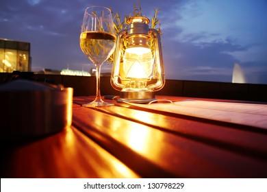 A glass of white wine besides a lantern.