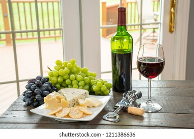 Glass of white wine with wine bottle, cheese and grapes