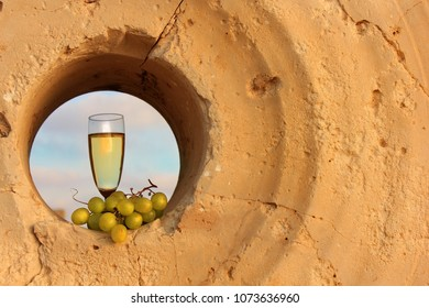 glass of white wine and a bunch of grapes inside the a millstone in the National Park Achziv, Israel
