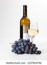 A glass of white wine, a bunch of grapes, an open bottle. White background.