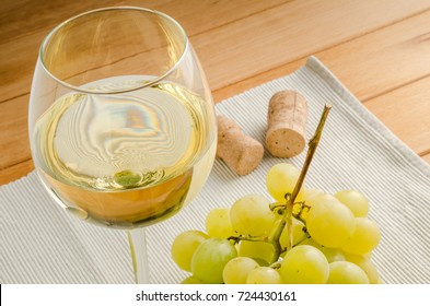 Glass of White Wine and a Bunch of Grapes on a Table. Two Corks are Visible in Background