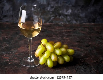A glass of white wine with a bunch of green grapes on a brown dark background. Alcoholic beverages.