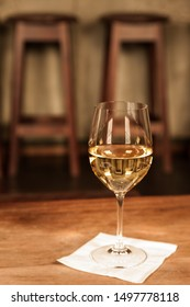 Glass of white wine Chardonnay on table in upscale bar restaurant with barstools in background. Selective focus on front edge of glass.