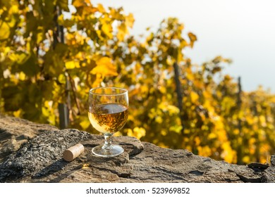 Glass of white wine and the cork on the old stone wall. Autumnal vineyard in Lavaux region, Switzerland.