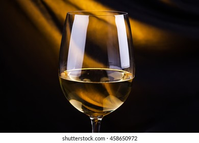 Glass of white wine with a dark background lit by a yellow light