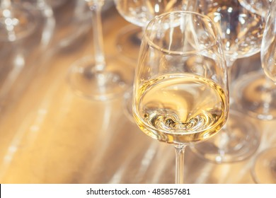 Glass of white wine with empty wine glasses in the background