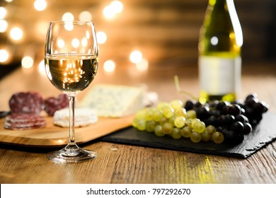 glass of white wine with french cheese and delicatessen in restaurant wooden table with romantic dim light and cosy atmosphere