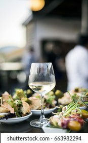 glass of white wine with gourmet food tapa snacks in outdoors bar at sunset