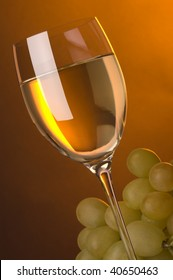 a glass of white wine and grape