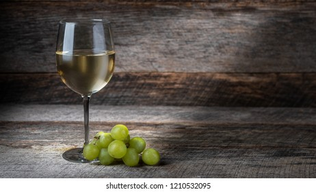 glass of white wine and grapes on wooden background