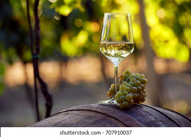 A glass of white wine with grapes on a barrel