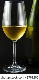 Glass of white wine and green wine bottle against a black background