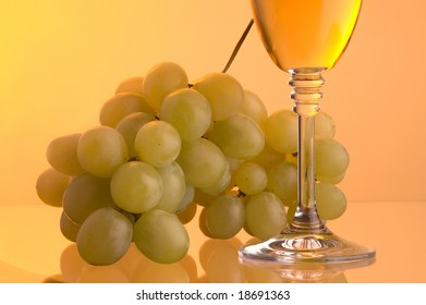 a glass with white wine and green grape