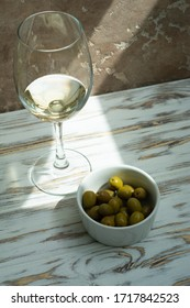 glass of white wine, green olives on a white wooden background provence breakfast in the garden apetizer