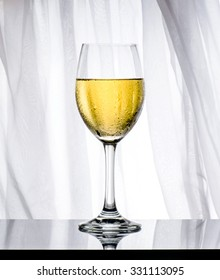 Glass of white wine, isolated. Grey background and marble table