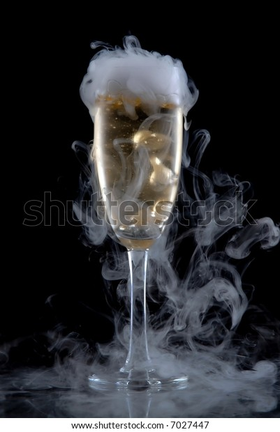 Glass of white wine isolated over black background, with a lot of smoke