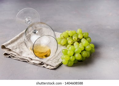 Glass of White Wine Lying on Napkin and Branch of Green Grapes on Gray Background Copy Space