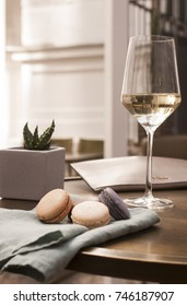 Glass of white wine with macarons on a napkin 2
