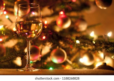 Glass of white wine next to a christmas tree