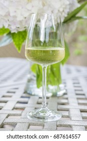 A Glass of White Wine on a Garden Table in Front of a Vase of White Hydrangea Flowers