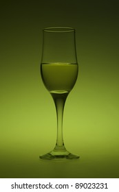 A glass of white wine on green background