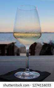 Glass of white wine on the horizon line.