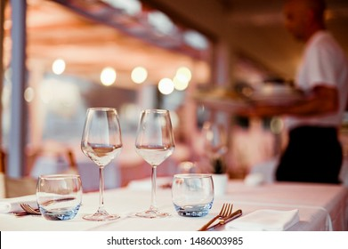 A glass of white wine on a table in a restaurant. Toned photo. Glare and light spots. Free space for text