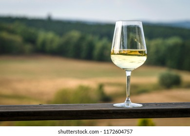 Glass of white wine on a wooden board in beautiful nature