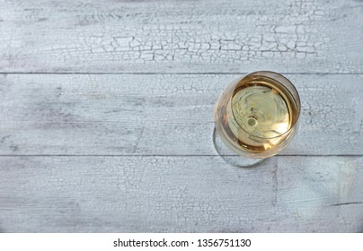 Glass of white wine on the wooden background