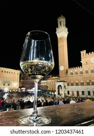 Glass of white wine in Piazza del Campo, Siena with the Mangia Tower