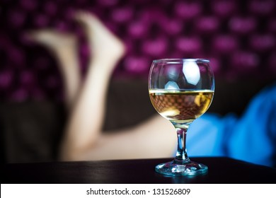 A glass of white wine - sexy women legs in the background
