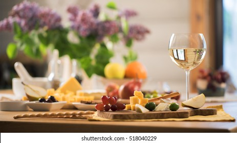 glass of white wine with a snacks stand on the kitchen table