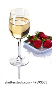Glass of White Wine With Strawberries on a Plate on a White Background