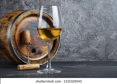 Glass with white wine for tasting and wooden barrel with corkscrew in dark cellar on gray concrete background