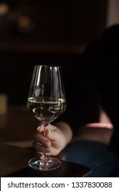 glass of white wine in a woman's hand