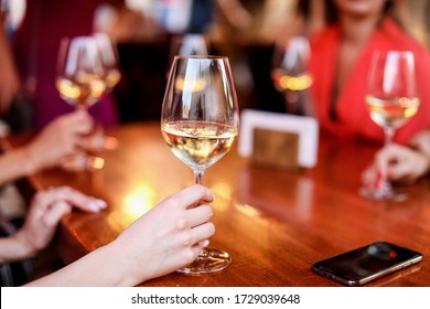a glass of white wine in a woman's hand at a party