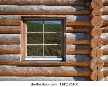 Glass window in a log wall in a sunny day