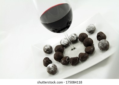 A glass of wine and assorted chocolates on a plate.
